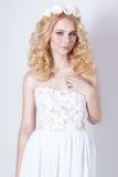 Bella giovane donna bionda elegante delicata adorabile nelle prendisole bianche chiffone ed in riccioli e una corona dei fiori in Immagini Stock