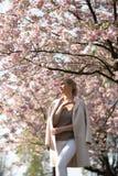 Bella giovane donna bionda nel parco di Sakura Cherry Blossom in primavera che gode della natura e del tempo libero durante lei c immagini stock