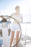 Bella giovane donna bionda sexy, guidante una barca sull'acqua, itinerario, bello trucco, abbigliamento, estate, sole, ente perfe Fotografie Stock Libere da Diritti
