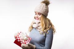 Bella giovane donna bionda in vestiti caldi di inverno con il contenitore di regalo a disposizione su fondo bianco fotografie stock
