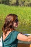 Bella giovane donna in blusa verde, occhiali da sole che si siedono sulla piattaforma di una barca Fotografie Stock Libere da Diritti