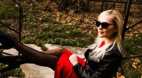 Bella giovane donna in bomber ed occhiali da sole neri Fotografia Stock