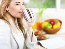 Bella giovane donna calma che mangia il caffè di mattina Fotografia Stock