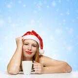 Bella giovane donna in cappello del Babbo Natale che si siede ai wi della tavola Fotografia Stock Libera da Diritti