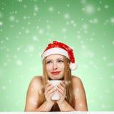 Bella giovane donna in cappello del Babbo Natale che si siede ai wi della tavola Immagine Stock