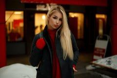 Bella giovane donna in cappotto d'avanguardia con la borsa che cammina vicino al negozio fotografia stock