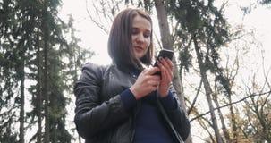 Bella giovane donna castana che prende un Selfie facendo uso di Smartphone Chiuda su della ragazza felice che usando Smartphone a video d archivio