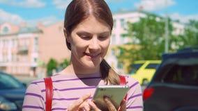 Bella giovane donna castana che usando vita urbana vivente di camminata delle vie della città di tecnologia dello Smart Phone archivi video
