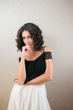 Bella giovane donna castana con il pensiero nero dei capelli ricci Immagini Stock