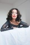 Bella giovane donna castana in gonna del nero del pizzo sullo shee bianco Fotografie Stock