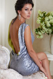 Bella giovane donna castana sexy con eleganza di trucco di sera governata portando un breve vestito da sera ricamato con argento fotografia stock libera da diritti
