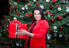 Bella giovane donna castana sorridente, stante vicino all'albero di Natale fotografia stock libera da diritti