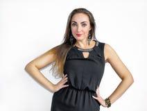 Bella giovane donna castana in vestito nero su un fondo bianco fotografia stock