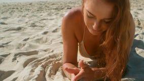 Bella giovane donna caucasica in bikini che si rilassa sulla spiaggia nel sole stock footage