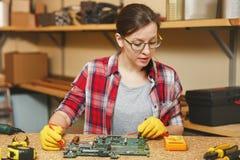 Bella giovane donna caucasica dei Brown-capelli che lavora nell'officina di carpenteria al posto della tavola fotografie stock