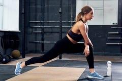 Bella giovane donna che allunga nella palestra di CrossFit Fotografia Stock