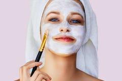 Bella giovane donna che applica maschera facciale sul suo fronte con la spazzola Cura e trattamento di pelle, stazione termale, b fotografia stock
