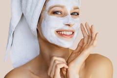 Bella giovane donna che applica maschera facciale sul suo fronte Cura e trattamento di pelle, stazione termale, bellezza naturale immagini stock