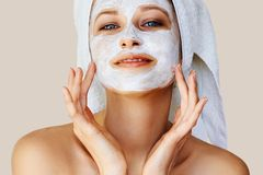 Bella giovane donna che applica maschera facciale sul suo fronte Cura e trattamento di pelle, stazione termale, bellezza naturale immagine stock