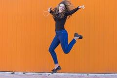 Bella giovane donna che ascolta la musica con le cuffie ed il salto Fotografie Stock Libere da Diritti