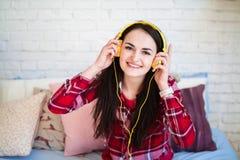 Bella giovane donna che ascolta la musica in cuffie a casa Immagine Stock