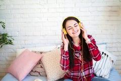 Bella giovane donna che ascolta la musica in cuffie a casa Fotografie Stock