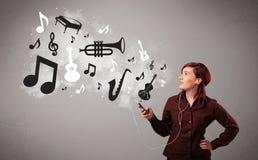 Bella giovane donna che canta e che ascolta la musica con il musica Immagini Stock