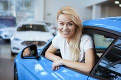 Bella giovane donna che compra nuova automobile alla gestione commerciale immagini stock