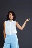 Bella giovane donna che controlla fondo grigio e che indica il suo dito Fotografie Stock Libere da Diritti