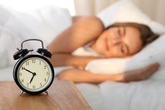 Bella giovane donna che dorme e che sorride mentre trovandosi a letto confortevolmente e beato sui precedenti dell'allarme Fotografie Stock Libere da Diritti