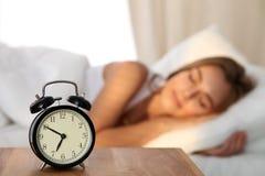 Bella giovane donna che dorme e che sorride mentre trovandosi a letto confortevolmente e beato sui precedenti dell'allarme Fotografia Stock