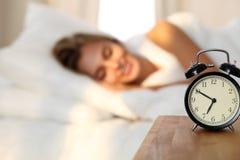 Bella giovane donna che dorme e che sorride mentre trovandosi a letto confortevolmente e beato sui precedenti dell'allarme Immagine Stock Libera da Diritti