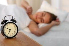 Bella giovane donna che dorme e che sorride mentre trovandosi a letto confortevolmente e beato sui precedenti dell'allarme Fotografia Stock Libera da Diritti