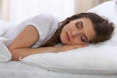Bella giovane donna che dorme mentre trovandosi nel suo letto e rilassandosi confortevolmente È facile da svegliare per lavoro o Fotografie Stock Libere da Diritti