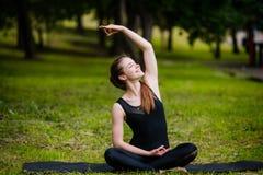Bella giovane donna che fa allungando esercitazione su erba verde alla sosta Allenamento di yoga Fotografie Stock
