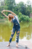 Bella giovane donna che fa allungando esercizio nel parco vicino al lago Fotografia Stock