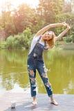 Bella giovane donna che fa allungando esercizio nel parco vicino al lago Fotografia Stock Libera da Diritti