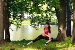 Bella giovane donna che fa allungando esercizio in parco vicino al fiume Fotografia Stock