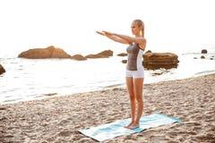Bella giovane donna che fa allungando gli esercizi durante l'yoga Immagine Stock Libera da Diritti