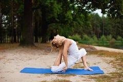 Bella giovane donna che fa esercitazione di yoga all'aperto fotografia stock