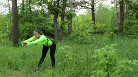 Bella giovane donna che fa esercizio nel giorno di estate del parco archivi video