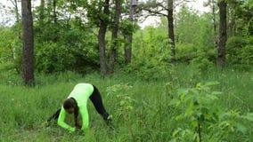 Bella giovane donna che fa esercizio nel giorno di estate del parco stock footage