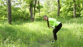 Bella giovane donna che fa giorno di estate del parco della testa di legno del whith di esercizio stock footage