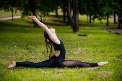 Bella giovane donna che fa rilassamento ed allungamento degli esercizi nel parco Immagine Stock Libera da Diritti