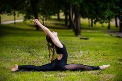 Bella giovane donna che fa rilassamento ed allungamento degli esercizi nel parco Fotografie Stock
