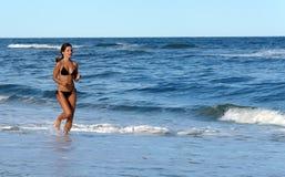 Bella giovane donna che funziona sulla spiaggia Fotografie Stock Libere da Diritti