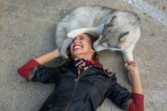 Bella giovane donna che gioca con il suo cane del husky sul pavimento fotografia stock libera da diritti