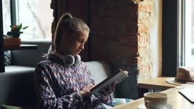 Bella giovane donna che gode del libro divertente nella lettura e nella risata del caffè video d archivio
