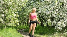Bella giovane donna che gode dell'odore in un giardino di fioritura della molla video d archivio