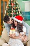 Bella giovane donna che guarda il contenitore di regalo e che sorride mentre il suo ragazzo fotografia stock